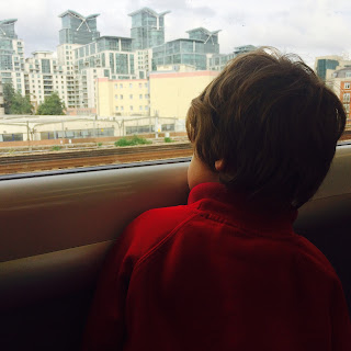 David, our autistic son, looking back through a window on a train journey