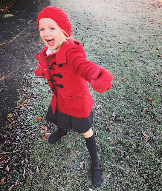 A 5 year old girl in red toggle coat, hat and gloves