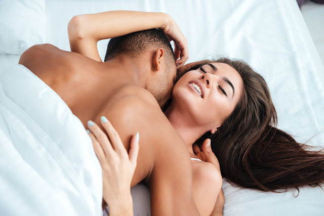 Gentle young couple lying and making love in bed