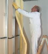 hobre colocando aislamiento acustico pared