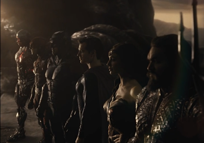The Justice League standing side by side, shot in a 3/4 view in order to fit them all in the frame.
