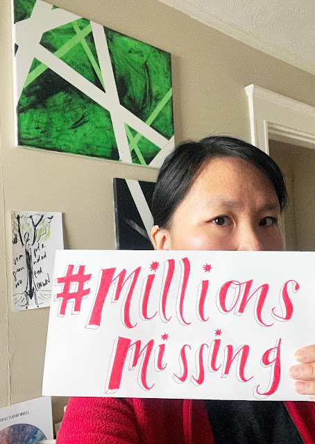 """A woman holds a handmade sign that says """"#Millions Missing"""" in red ink. The lower part of her face is partially covered by the sign, and the part you can see is half in light, half in shadow."""