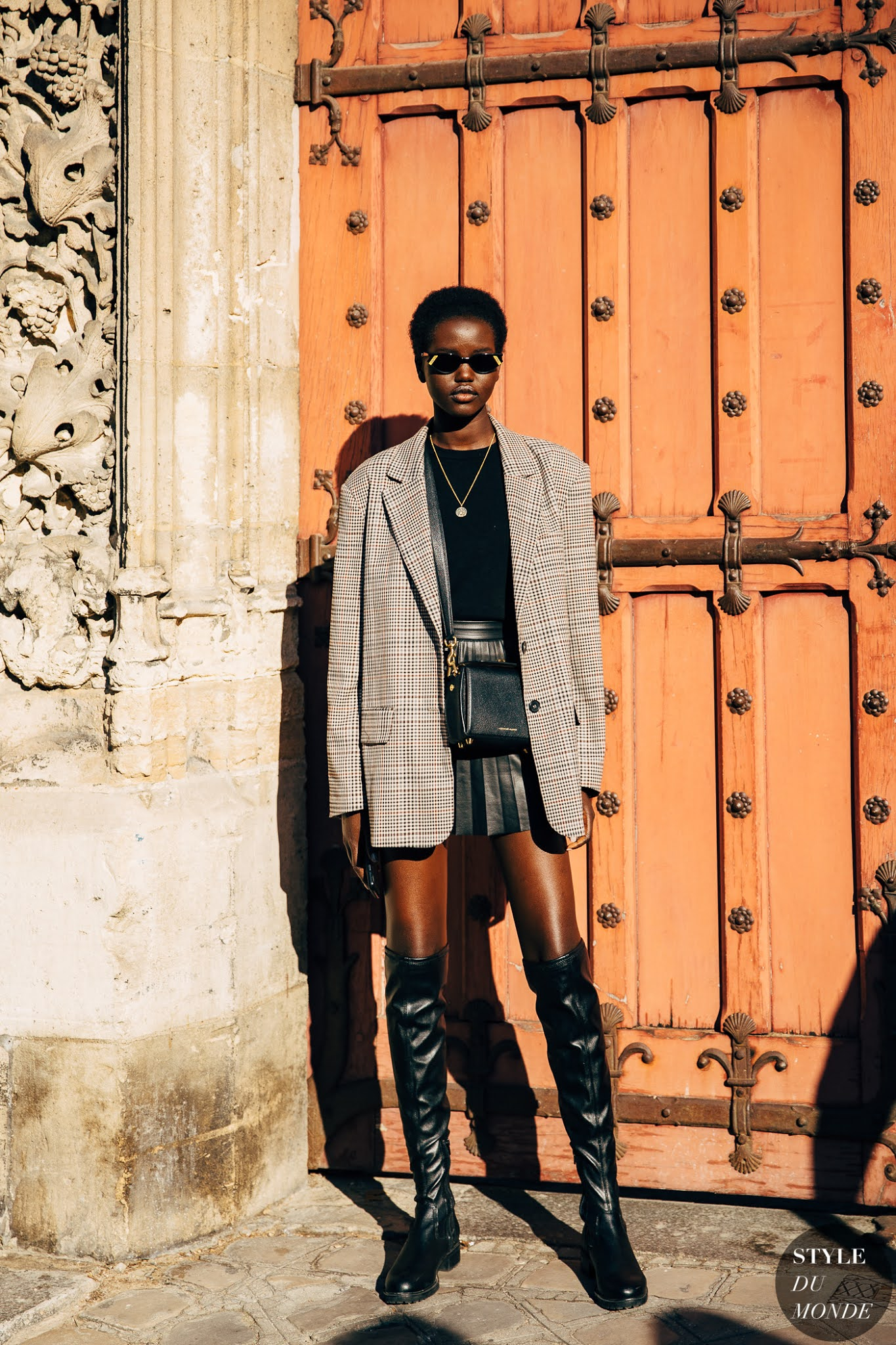 25 Best Over-the-Knee Boots for Fall and Winter — Model Adut Akech Bior street style outfit with plaid blazer and pleated leather skirt
