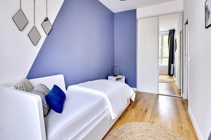 Pared pintada en blanco y azul con efecto triángulo.