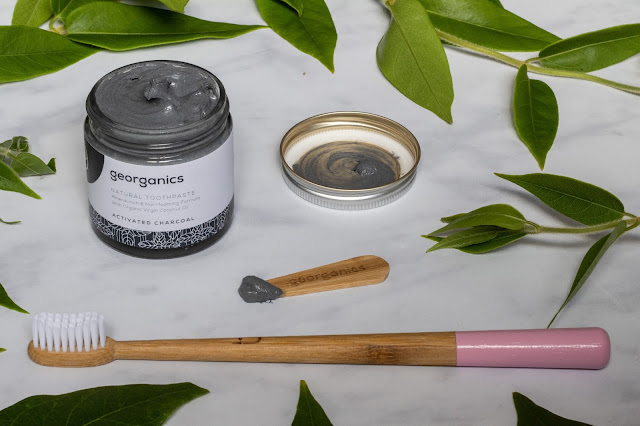 An open jar of georganics charcoal activating toothpaste, the bamboo applicator and bamboo toothbrush