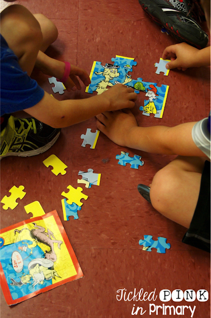 students putting together a Dr. Seuss puzzle on the tile floor