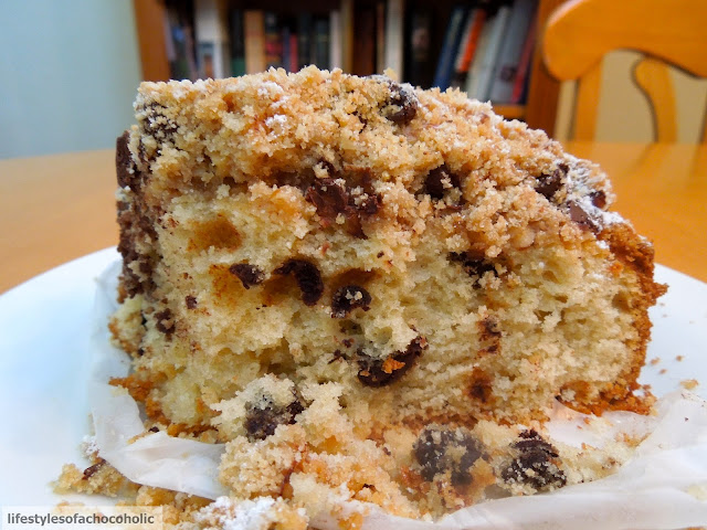 slice of sour cream coffee cake half eaten on a white plate with chocolate chips falling out