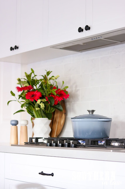 Shaker Kitchen with Gas Cooktop and Undermount Range Hood and Blue Dutch Oven on Stove