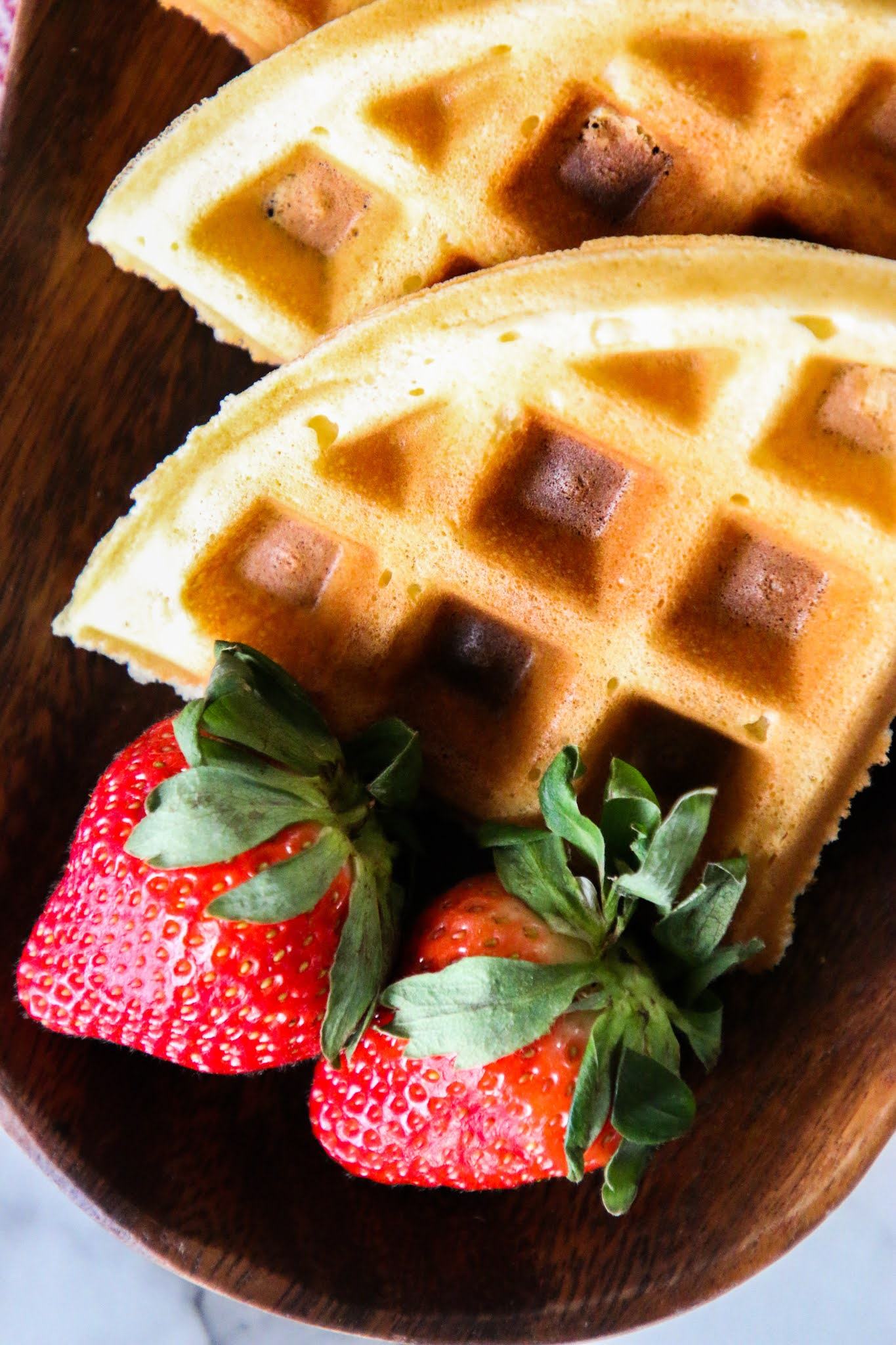 Four waffle triangles on a wood platter with strawberries and a red striped towel in the background.