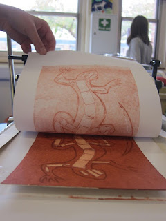Photograph of student peeling their print of a lizard away from the print board after printing