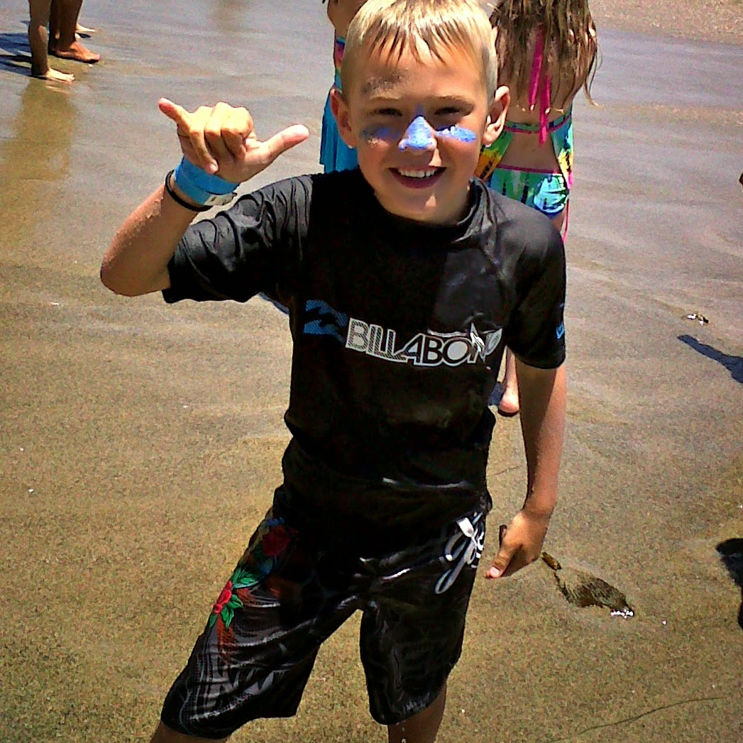 "Young boy at Aloha Beach Camp giving the ""Hang Loose"" sign on the beach at  Paradise Cove."