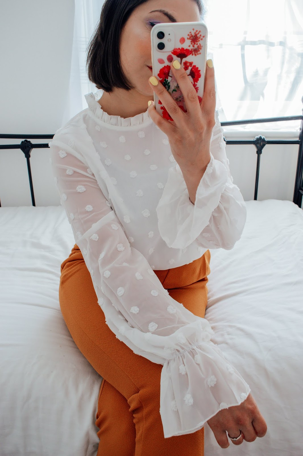 Person holding a phone wearing a white blouse and burnt orange trousers.