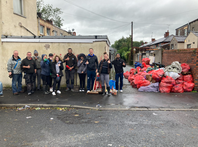 volunteers posing proudly next to a pile of rubbish that has been collected from local alleyways and streets