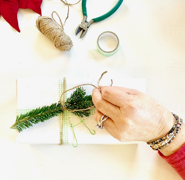 Tying on string, fresh greenery and tag on a christmas wrapped gift