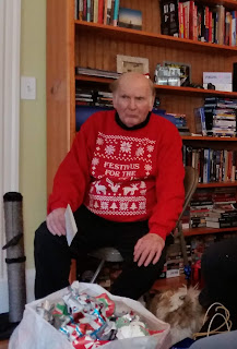 "Tod Eaton sitting in a chair wearing a ""Festivus"" sweater."