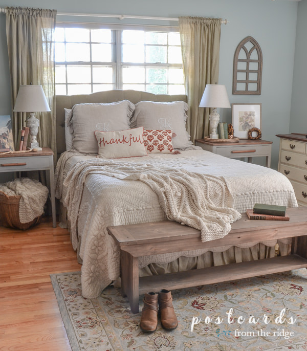 bedroom with French quilt, blue rug, fall pillows