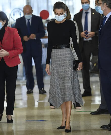 Queen Letizia wore a check wool skirt from Massimo Dutti, and black cashmere sweater from Hugo Boss. Carolina Herrera pumps and clutch