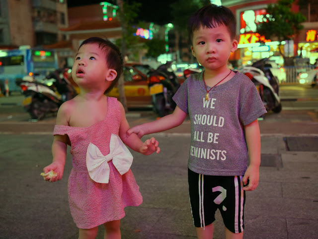 "a child wearing a ""We should all be feminists"" shirt holding the arm of a child wearing a dress with a large white bow"