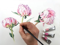 A hand holding a paintbrush painting pink and white flowers. There are also tubes of paint on the lower right.