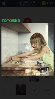 Девочка на кухне на столе осуществляет готовку еды, раскатывая тесто