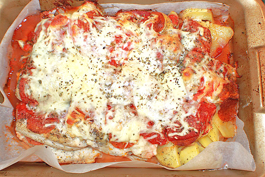 This is a pan of chicken pizza with potatoes baked in tomato sauce, herbs and melted cheese