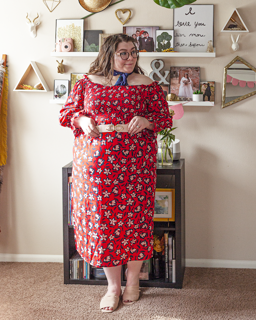 An outfit consisting of a navy blue square neck scarf tied around the neck, an off the shoulder red with navy blue outlined white flowers shirred bodice A-line midi dress with long bishop style sleeves, belted with a pink belt and pink slide sandals.