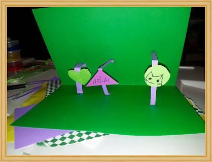 """En la imagen se puede observar un trabajo realizado con la técnica pop up. Se trata de una tarjeta confeccionada con cartulina de color verde que al abrirla sobresale en el centro un corazón verde,  un triángulo rosa que dice """"Hola"""" y un círculo  de color verde claro que tiene el dibujo en marcador de un gatito"""