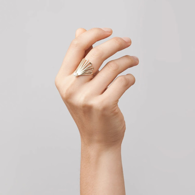 Close up of hand wearing a gold pearl fan ring.