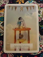 Card 37: Never ending story features a fairy sitting atop a sand clock