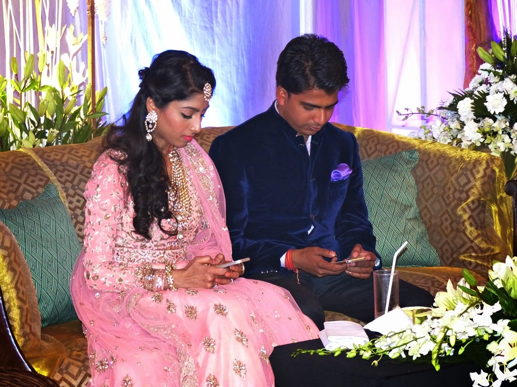 Bride and groom checking their phones during reception