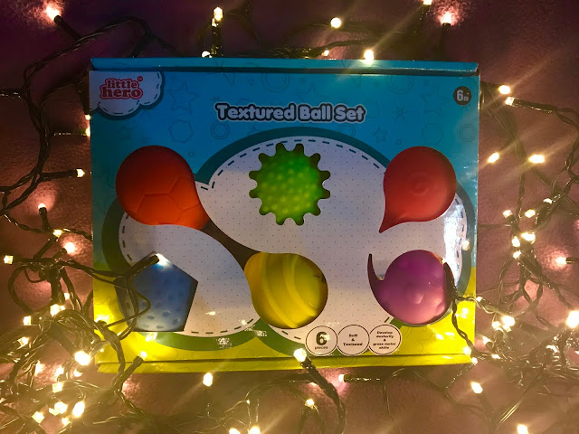 A box with 6 multi coloured balls with different textures surrounded by fairy lights