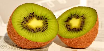 A kiwifruit cut in half, showing the green flesh inside.
