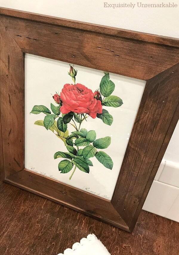 Red Vintage Floral Print framed leaning on wooden vanity top