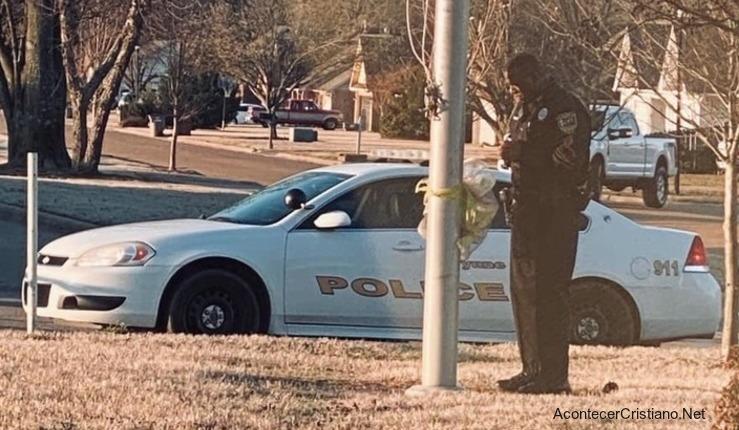 Policía orando frente a escuela