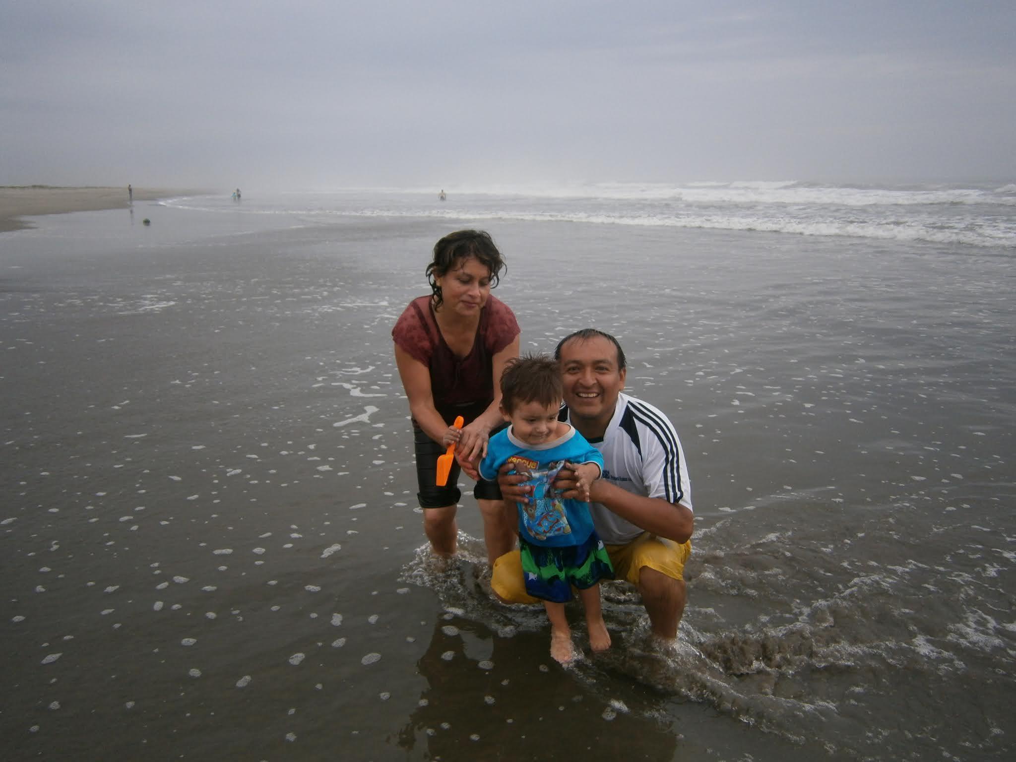 Descripción de la fotografía. Familia Alegre posando para la foto en la orilla de la playa. Familia alegre posando para la foto en la orilla de la playa acompañado de su niño.