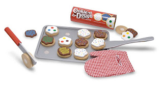A cookie baking playset that has a sheet tray, cookies, spatula and an oven mitt.