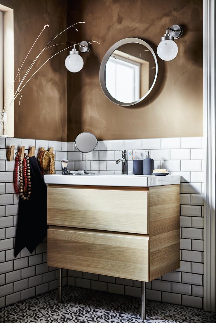 Novedades catálogo IKEA 2021 en baños: baño semialicatado con mueble blanco y pared oscura.