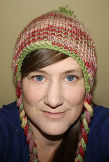 Free knitting pattern author modeling the Earflap Hat in a multicolor set.