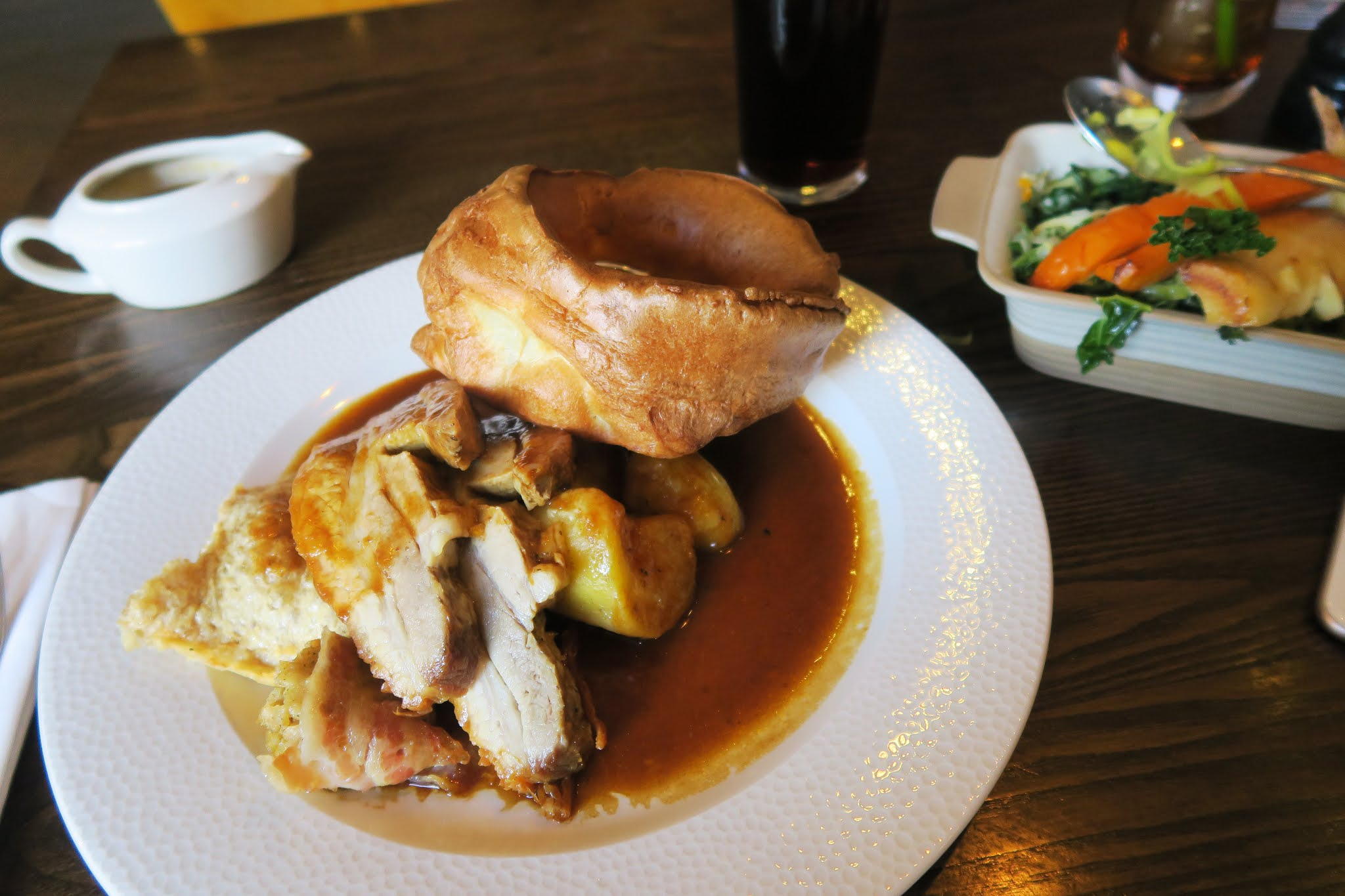 A large plate of meat, roast potatoes, and a large Yorkshire pudding. A bowl of vegetables can be seen in the background.
