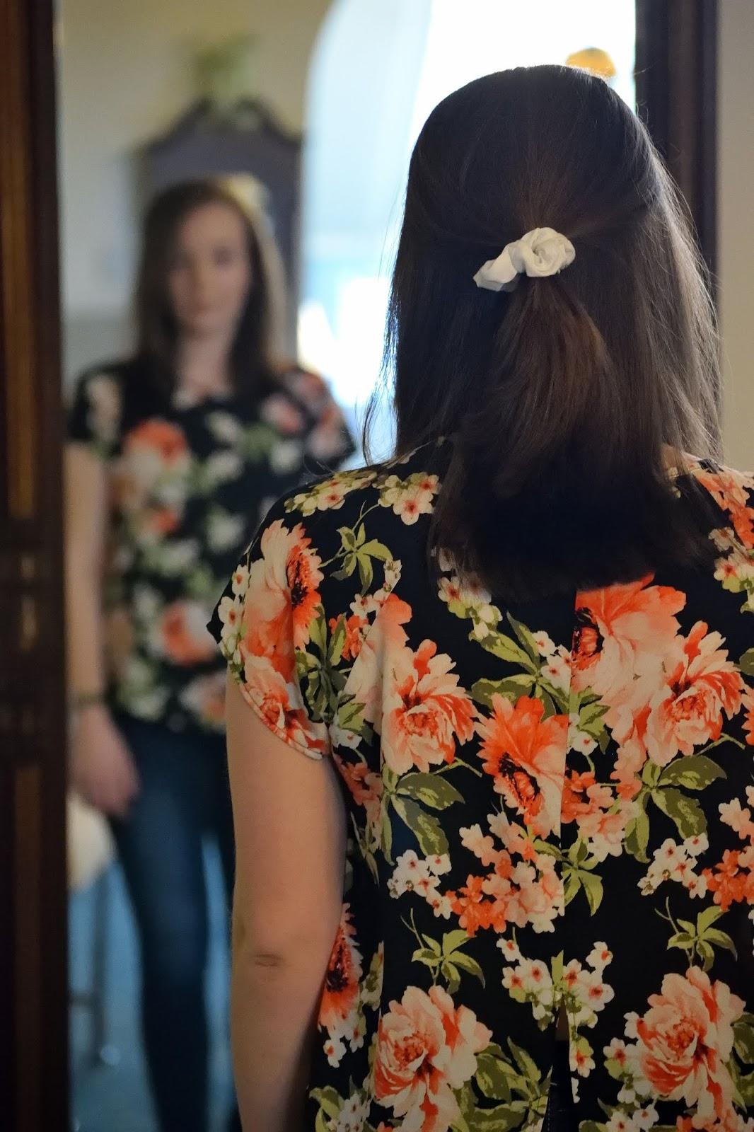 donna davanti allo specchio in jeans e maglietta floreale