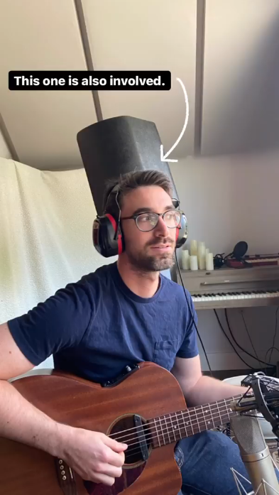 Jesse with headphones and a guitar in a studio with speakes and a keyboard behind him with the text 'this one is also involved'