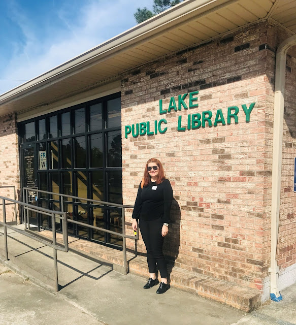 A woman wearing sunglasses smiles at the camera. She is posed in front of a building bearing the sign Lake Public Library.