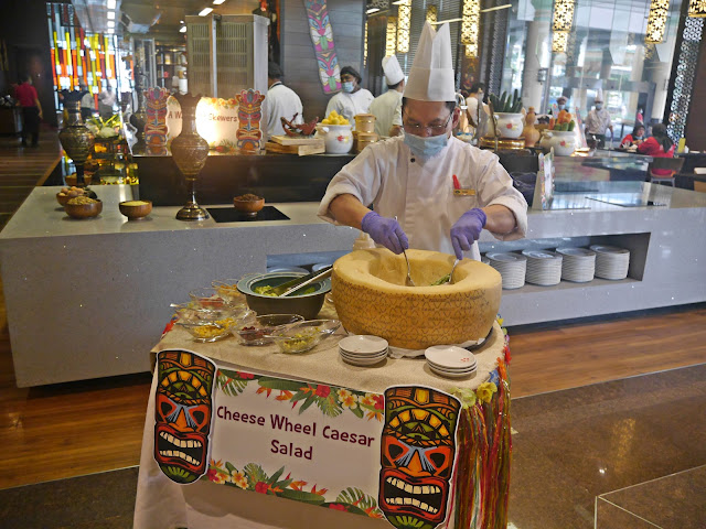 The chef tossing the Caesar Salad in the Cheese Wheel