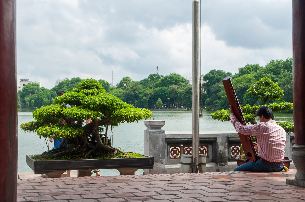 image of a girl playing the instrument in the temple near the hanoi lake