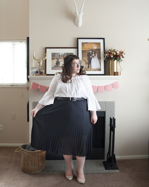 An outfit consisting of a white off the shoulder blouse with long sleeves and ruffle neck line tucked unto a black pleated midi skirt and beige slingback heels.