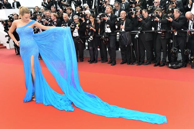 Blake segurando a cauda de seu vestido enquanto fotografos tiram as fotos