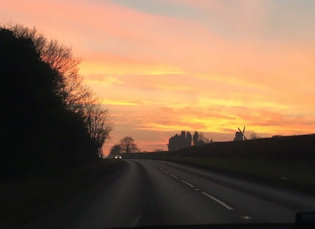 Morgan's Milieu | Leaving the Novel Behind: A photograph of the sky at sunset. A darkened windmill in the distance and a car on the road.