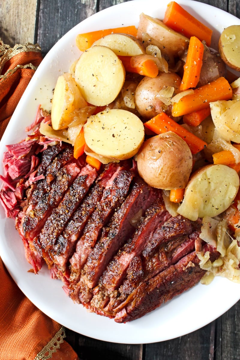 Top view of sliced corned beef next to carrots and potatoes on a white plate with an orange napkin next to it.