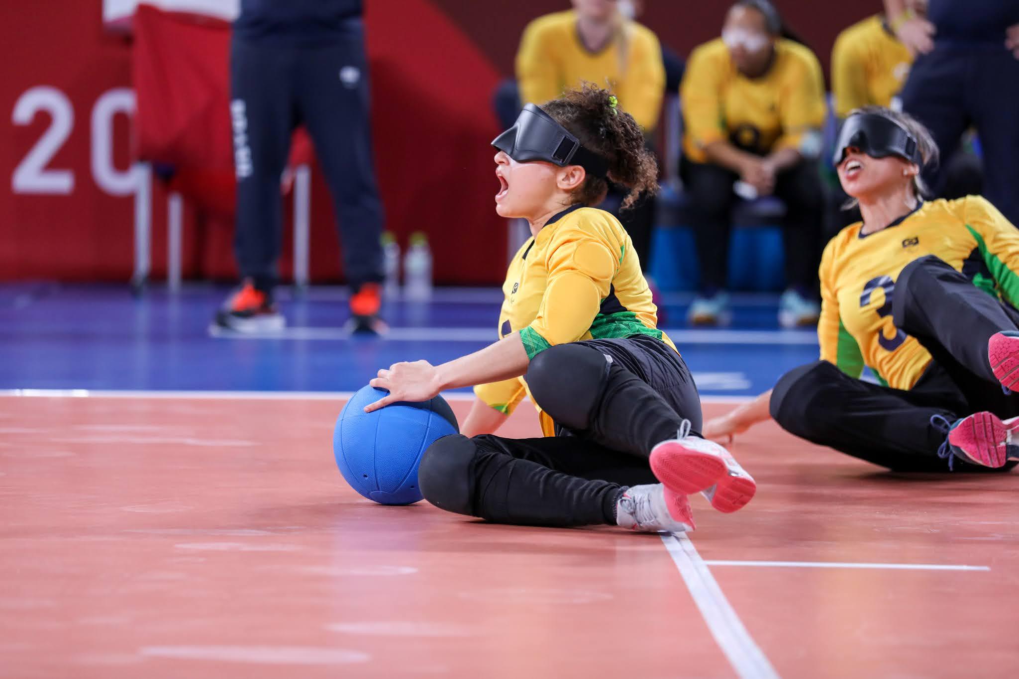 Jogadoras da seleção brasileira de goalball feminino, de uniforme amarelo, deitam no chão e arragam a bola