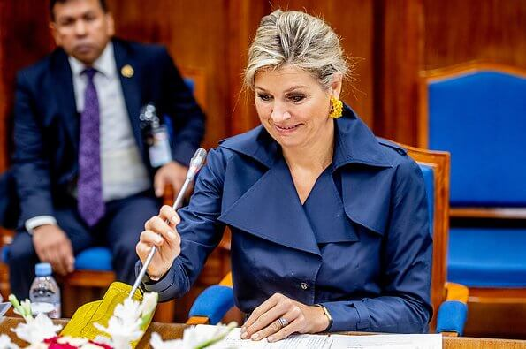 Queen Maxima wore a navy blue trench dress by Jan Taminiau. yellow earrings and Gianvito Rossi yellow metallic pumps